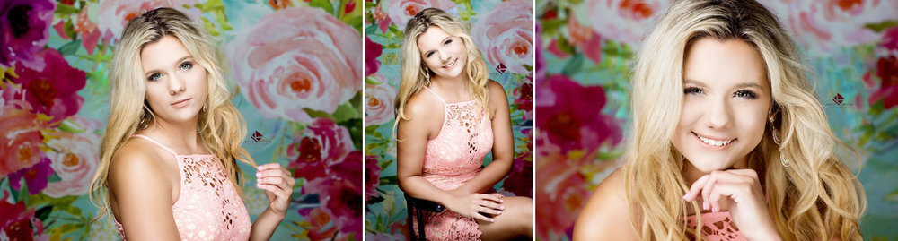 blonde senior girl in a pink, lace dress posing in front of a colorful, floral background at Katie Swatek Photography's studio in Wagner, SD
