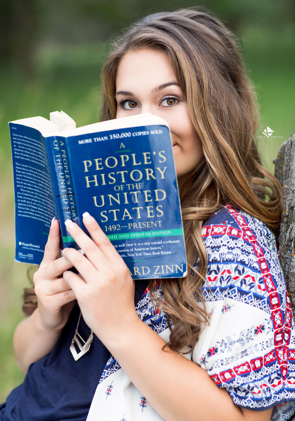 brunette senior girl holding a history book in front of her face