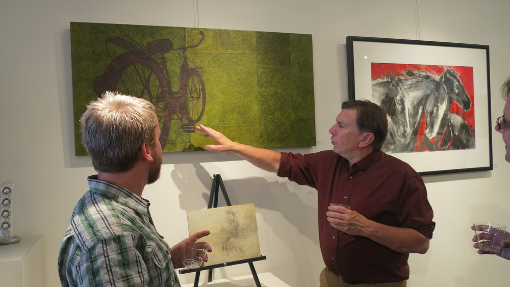 Artist Grant Penny telling a guest about his process. April 3rd, 2015 Pictured: Destination Unnecessary by Grant Penny, paper collage on cradled panel