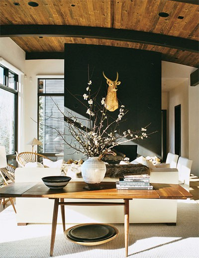 Image above (via Vogue) | The wood tone of the ceiling is repeated in the table and other wood furnishings in the space. The black of the fireplace wall is repeated in the window and door frames and the ceiling beams. Things are communicating here, connecting, to create balance.