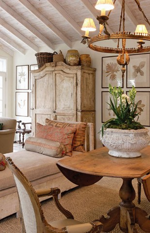 The large olive jars and baskets create a textural mass that extends the height of the armoire. Designer:  Jeffrey Bilhuber