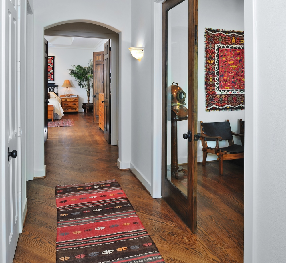 Hallway to Master Bedroom with red rug, Designer: Carla Aston