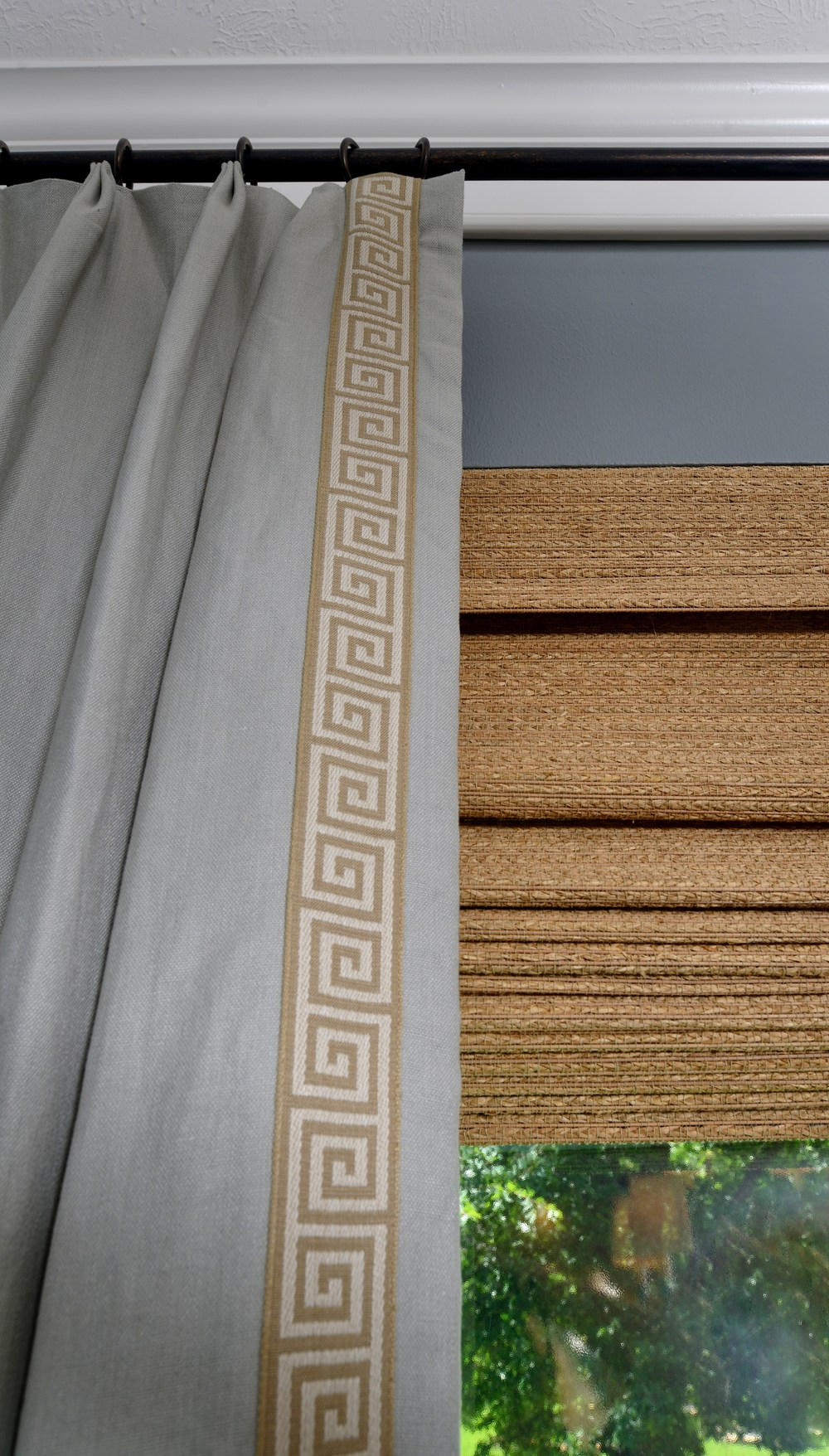 Custom window treatment with Greek key trim and woven wood shades, Designer: Carla Aston