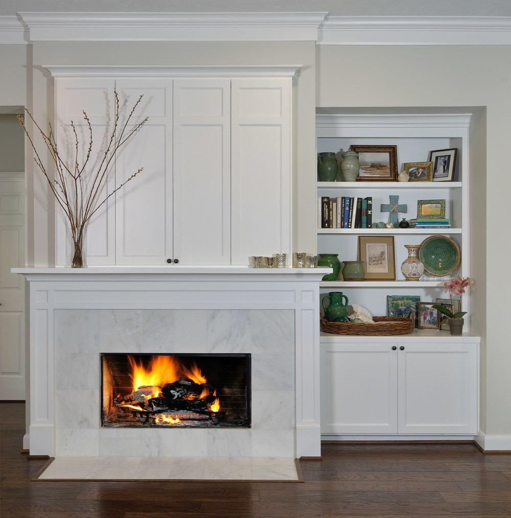 TV cabinet above fireplace with white marble surround, Designer: Carla Aston