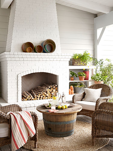 Outdoor mantel decorated with baskets. | Interior Designer: Victoria Pearson