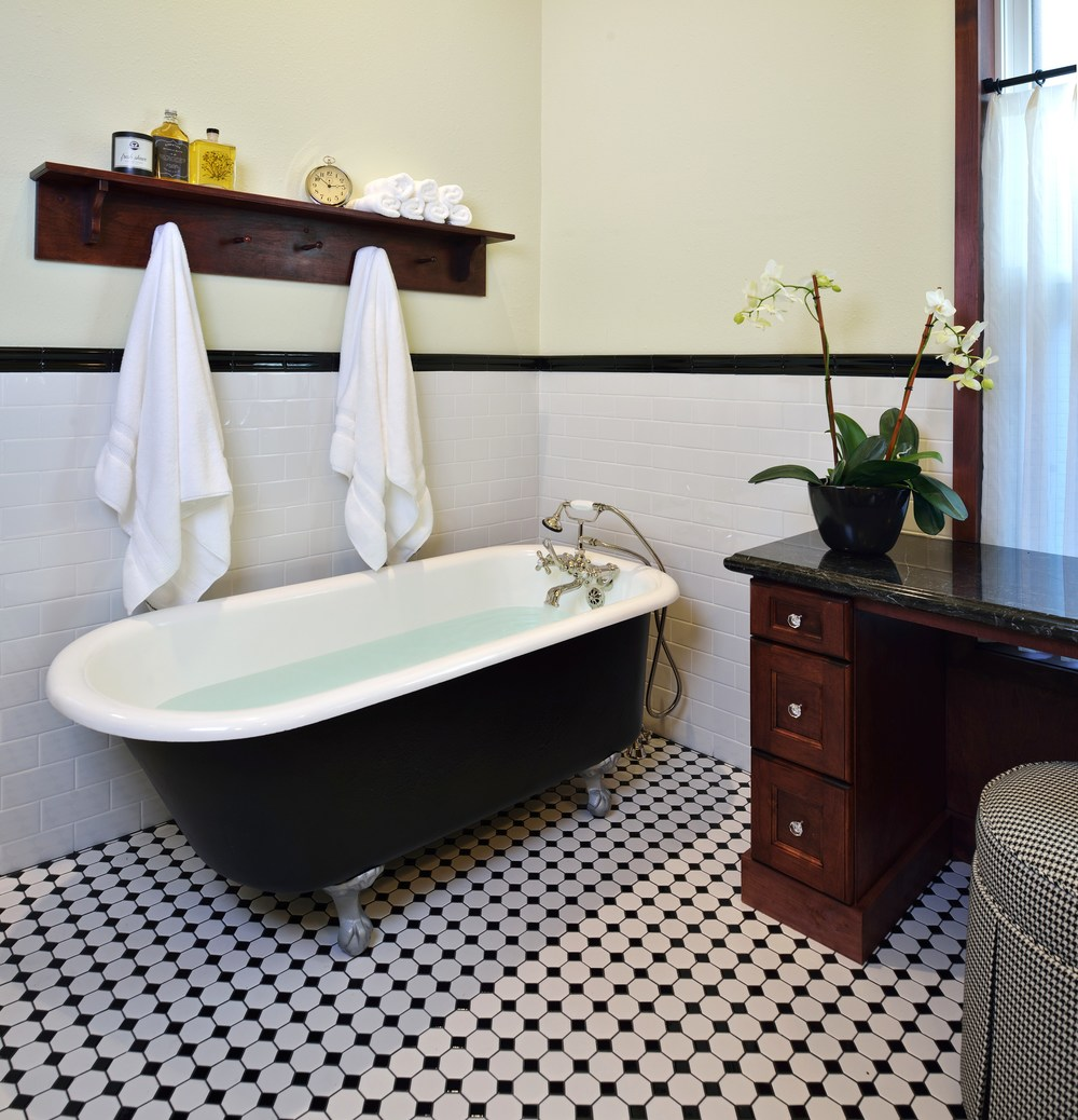 Vintage-inspired master bathroom | Interior Designer: Carla Aston / Photographer: Miro Dvorscak / tile, black and white, subway tile, black marble, houndstooth, footed tub