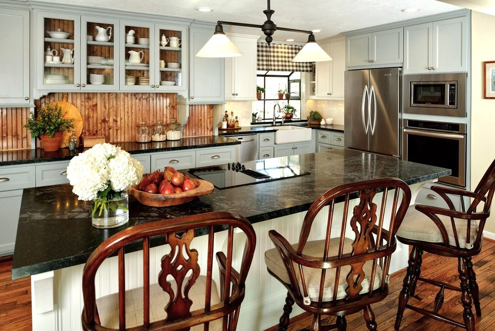 Before & After: A cottage / country style kitchen enjoys wide open space | Interior Designer: Carla Aston / Photographer: Miro Dvorscak — soapstone counters, island; white and gray cabinet; hardwood floor; lighting; hutch