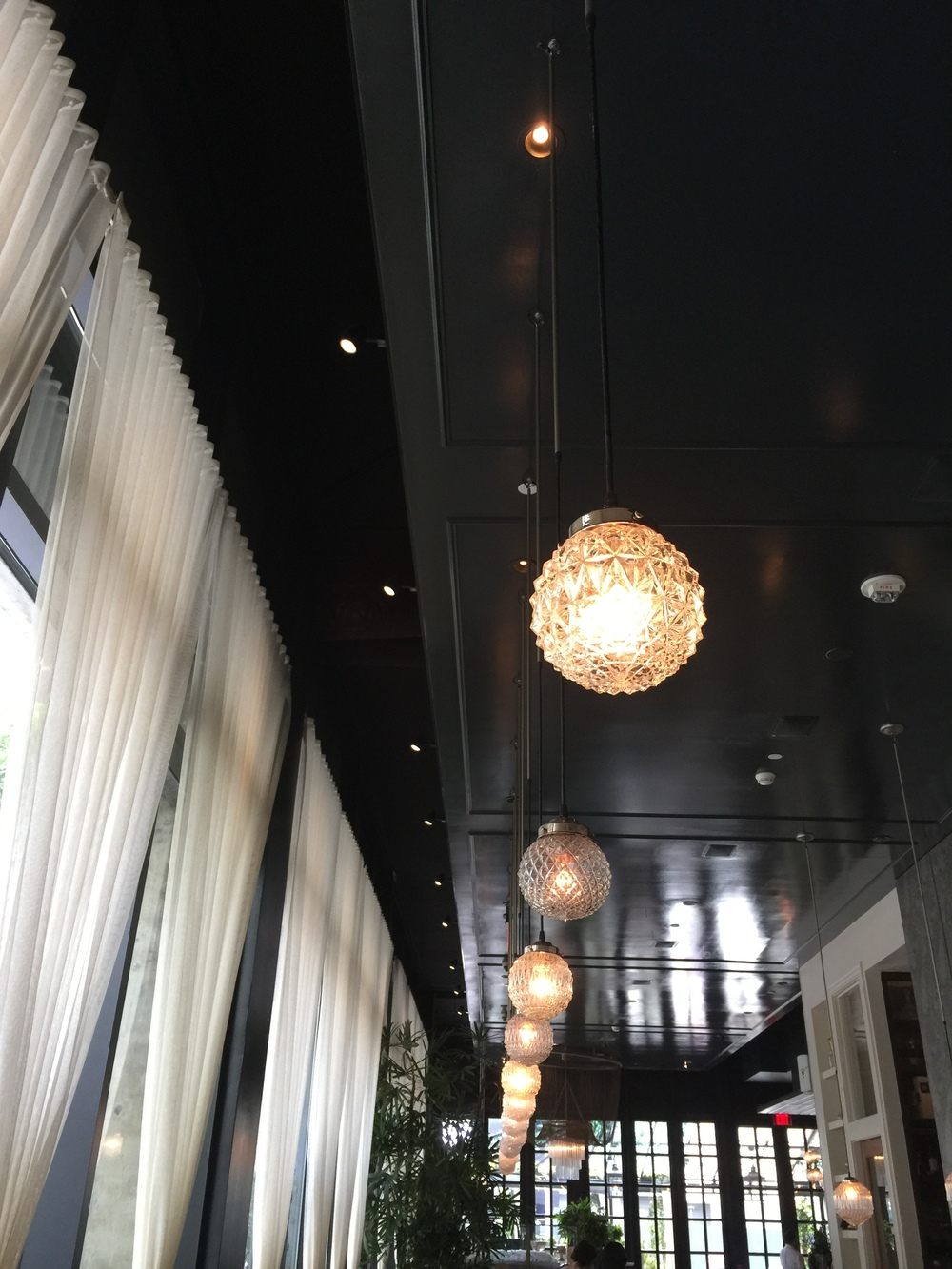 "Glossy dark ceiling sets off pendants @ Los Angeles' ""Faith & Flower"" restaurant, designed by Avroko."