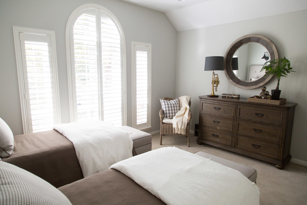 Guest Bedroom w/ horn lamp and round mirror, Designer: Carla Aston
