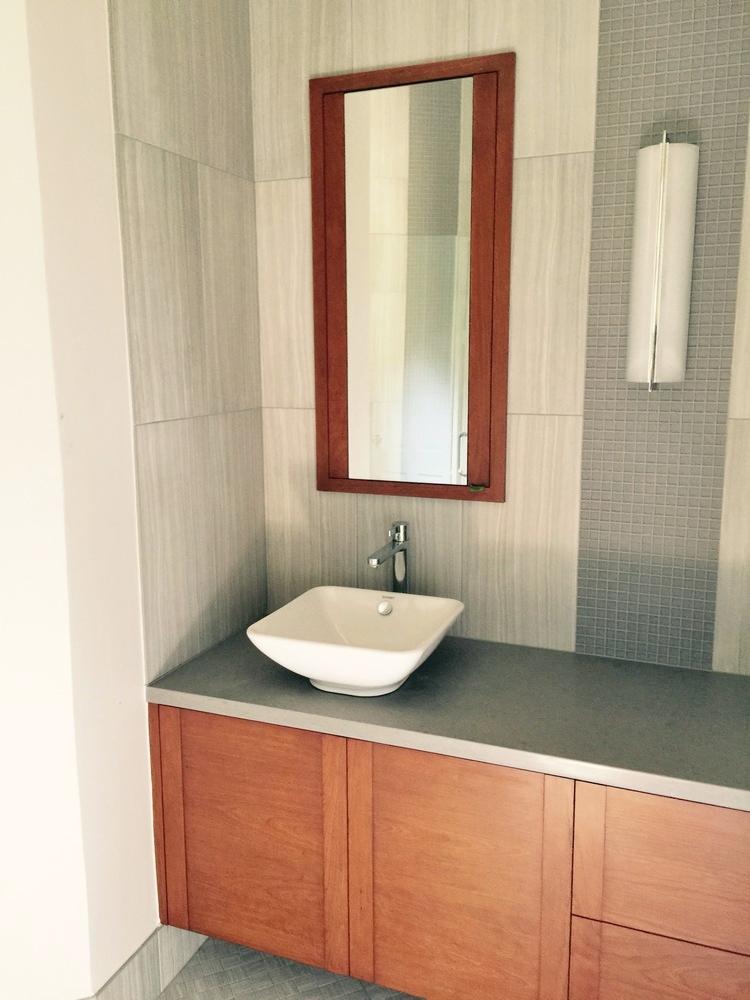 Guest bath w orange tone wood contemporary cabinetry | Interior Designer: Carla Aston