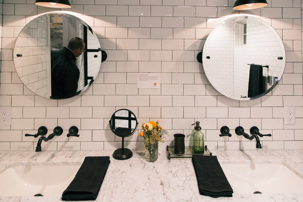 Master Bath Vanities, black and white, round mirrors, wall mount faucet | Interior Designer: Bobby Berk