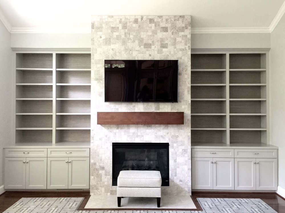 Grey cabinetry and stone used on fireplace wall remodel, Designer: Carla Aston