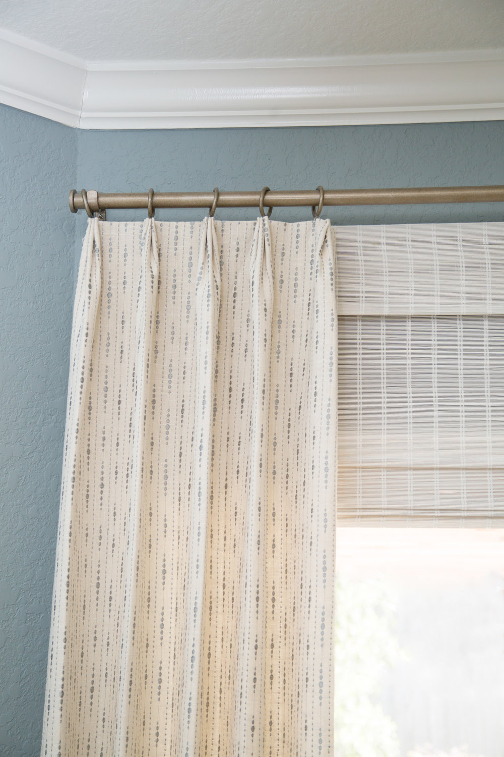 Window treatment with woven wood shades and stationary drapery panels