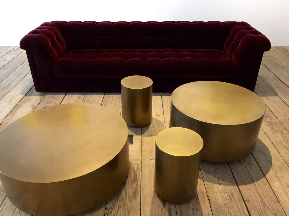 Stunning brass drum tables with a velvet tufted sofa