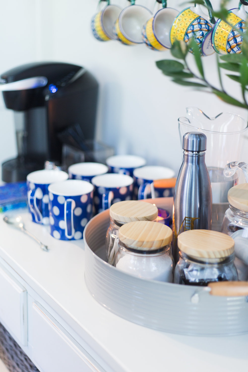Coffee bar station with blue mugs, tray, and containers from At Home stores