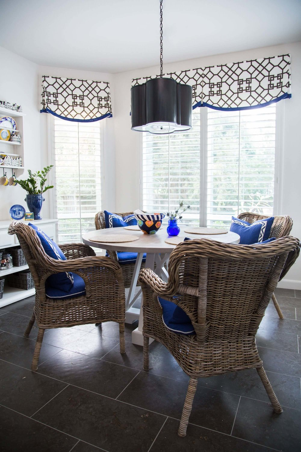"Breakfast room w/ custom window valances and edge banding, Ikea wicker chairs, round ""X"" base table and Circa Lighting Basil pendant. Before and after kitchen remodel - Carla Aston, Designer"