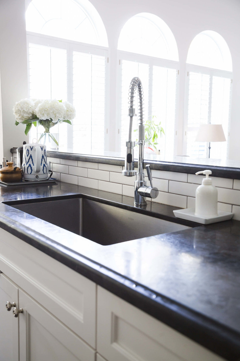 White kitchen with subway tile backsplash and pro style kitchen faucet, Designer: Carla Aston