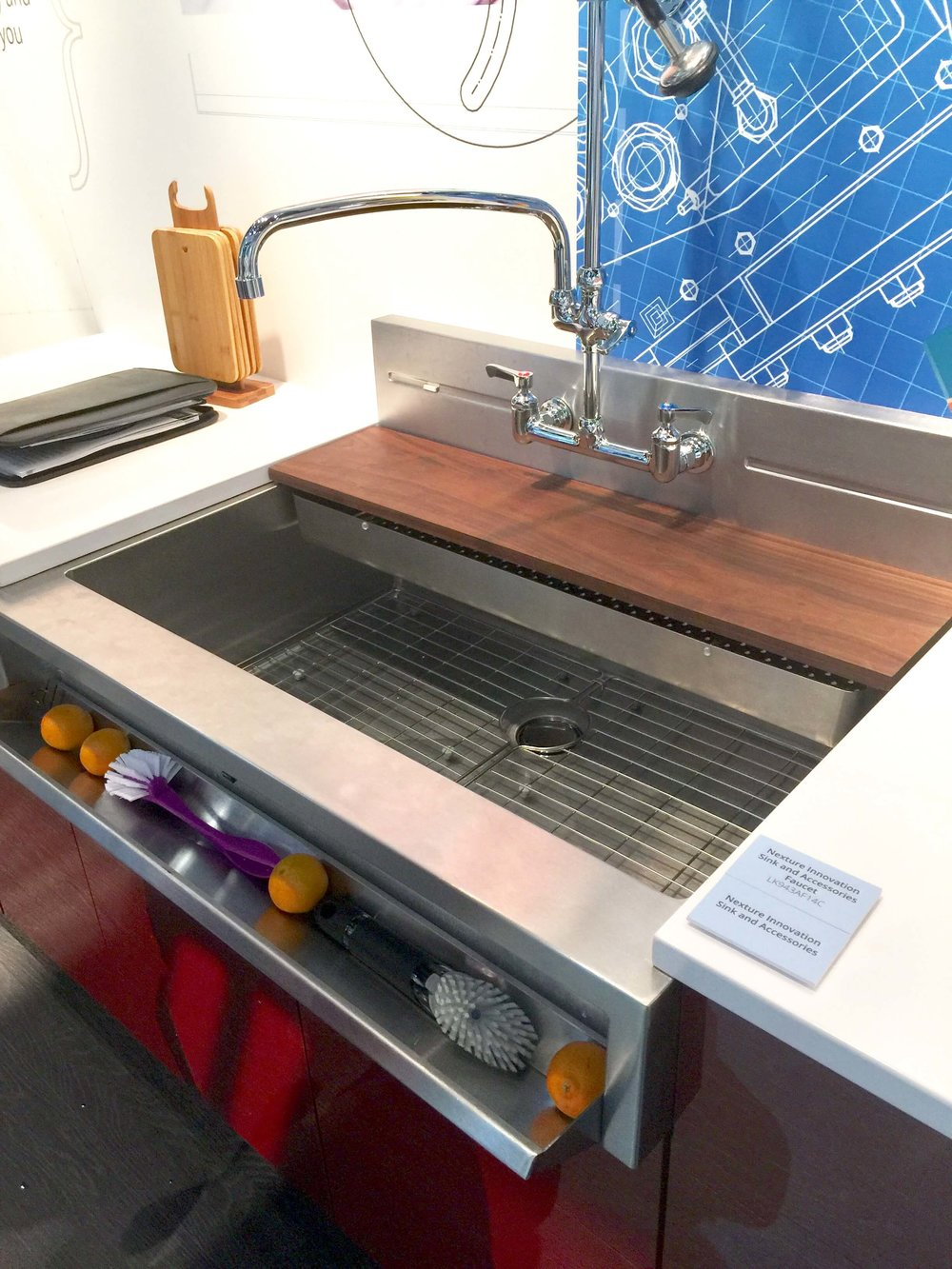 Elkay stainless steel prototype sink with tip out storage, sliding chopping board and strainer and stainless splash w/ wall mount faucet.