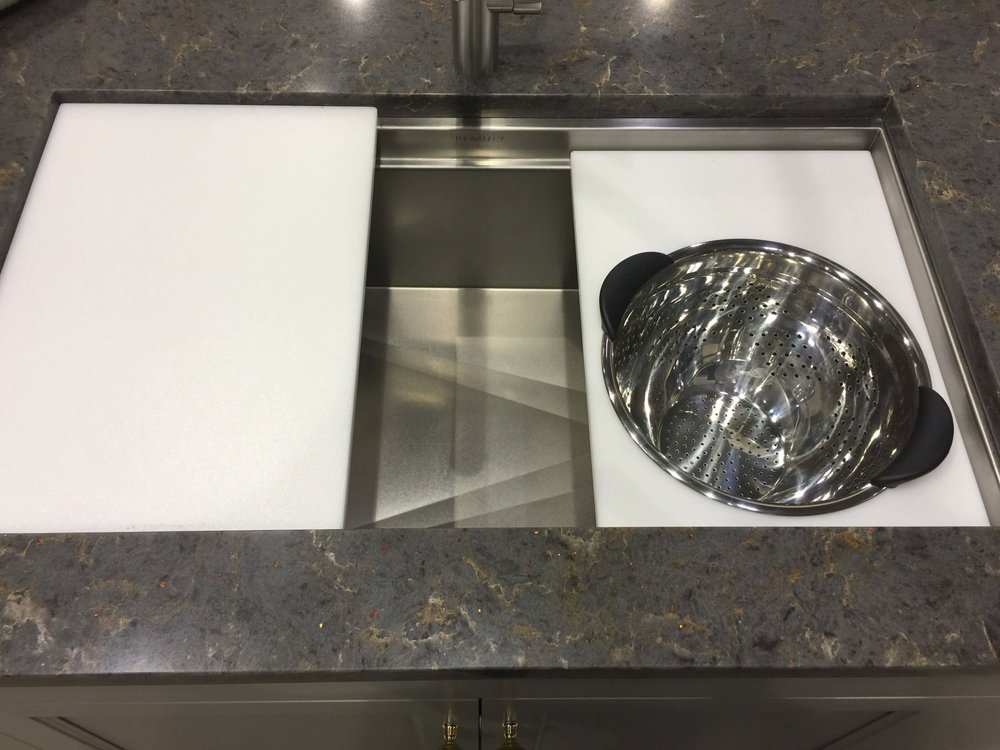 Stainless steel wide kitchen sink with chopping boards and colander