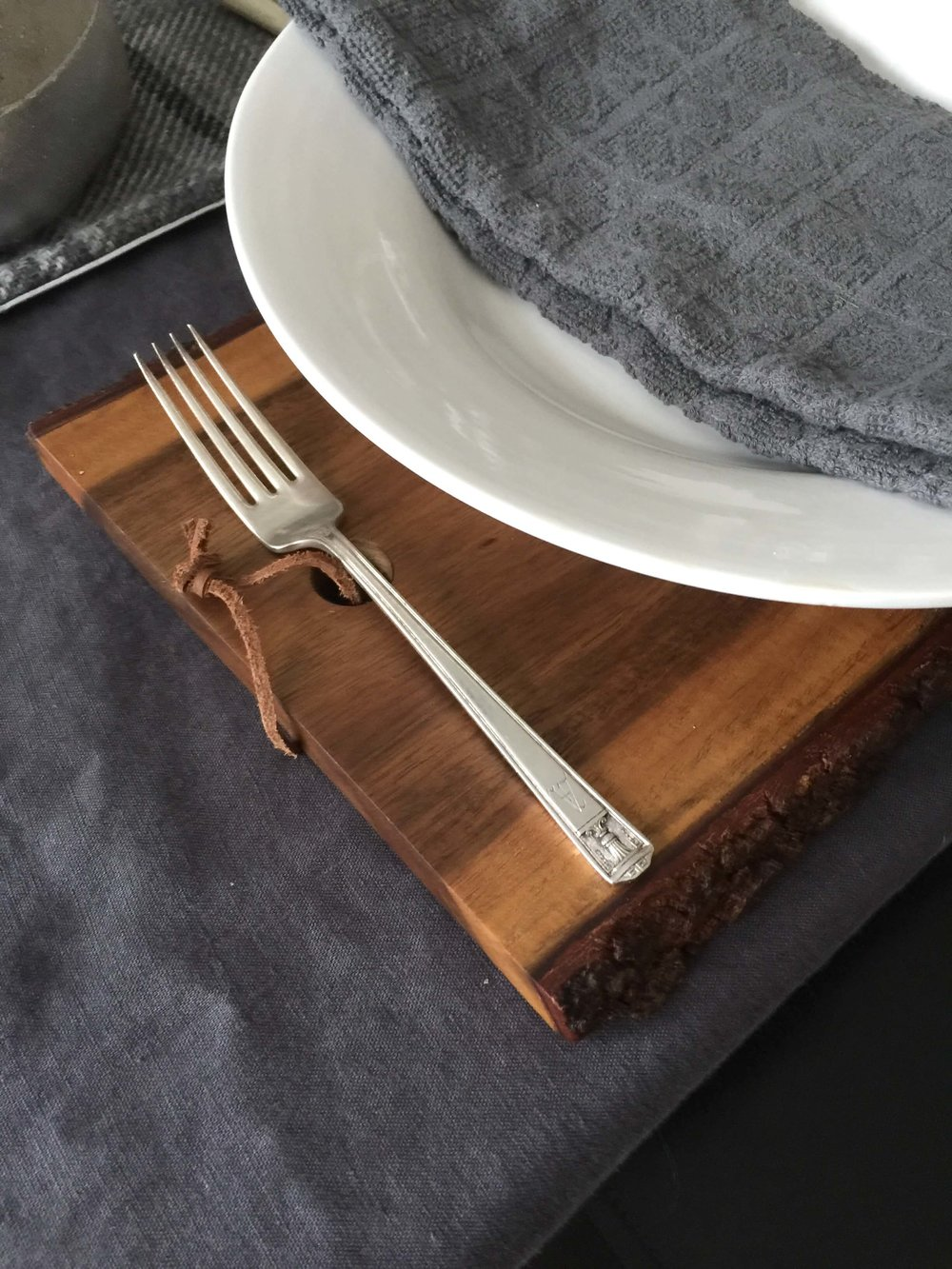 Winter tabletop with live edge cutting board and silver flatware | Carla Aston