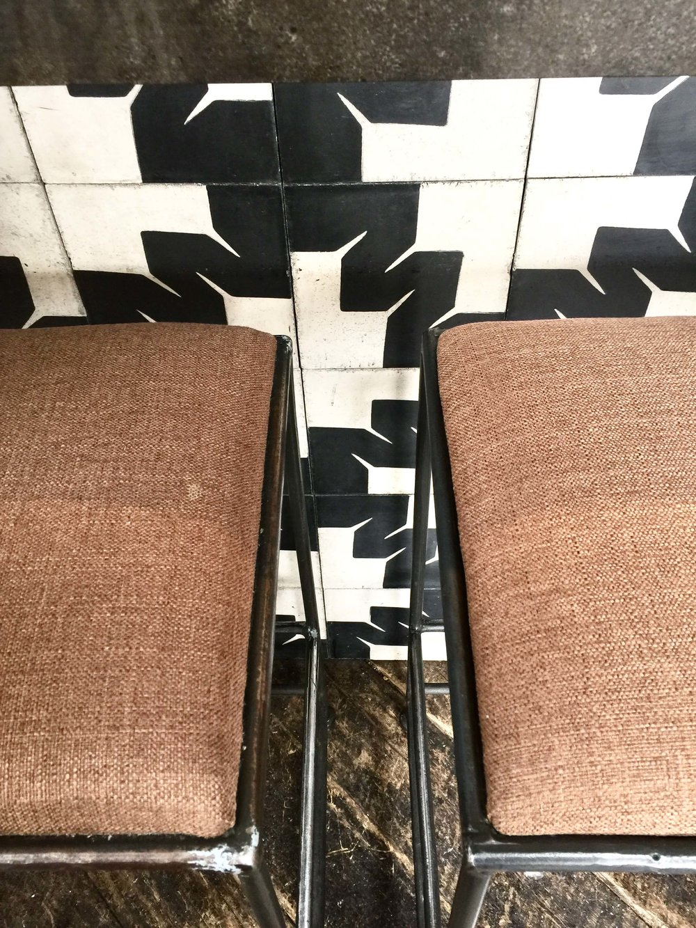 Graphic black and white tile at the bar face with rustic wood flooring