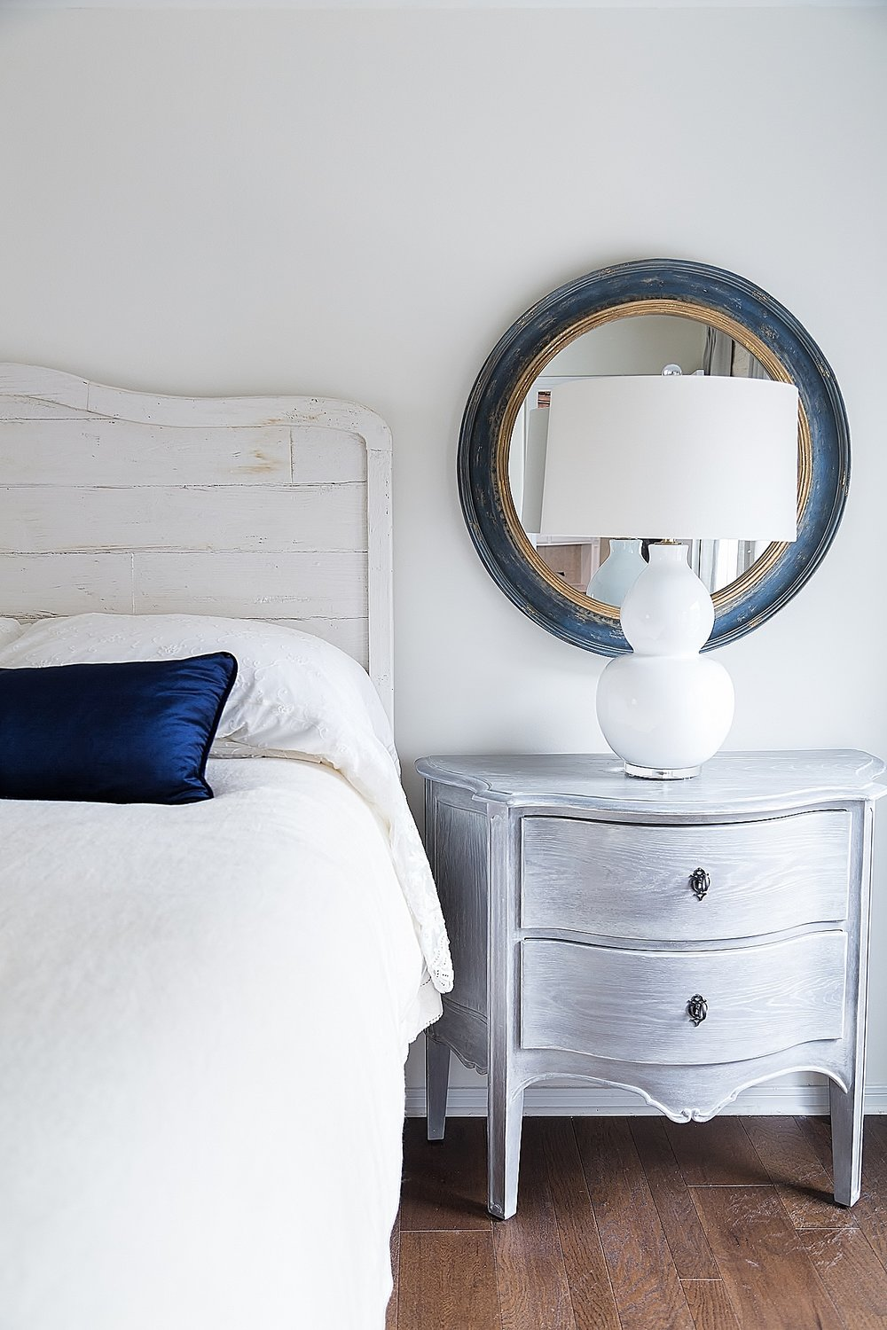 Gray nightstand in creamy white bedroom with navy mirror and pillow | Designer Carla Aston | Photo by Tori Aston