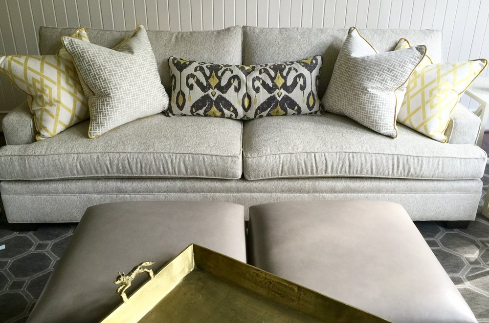 Gray sofa, rug, and ottomans with brass tray and yellow pillows | Designer Carla Aston