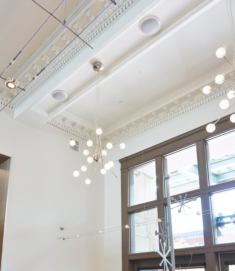 Mod lighting contrasts with the detailed moulding and architecture in Snooze | The Crawford Hotel.