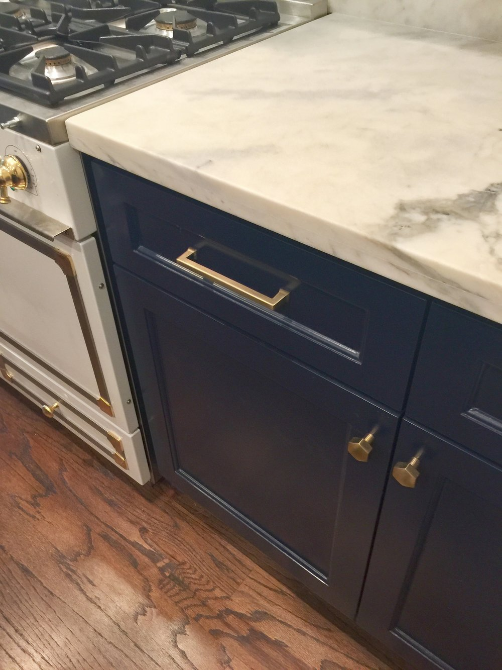 brass cabinet pulls on navy cabinetry