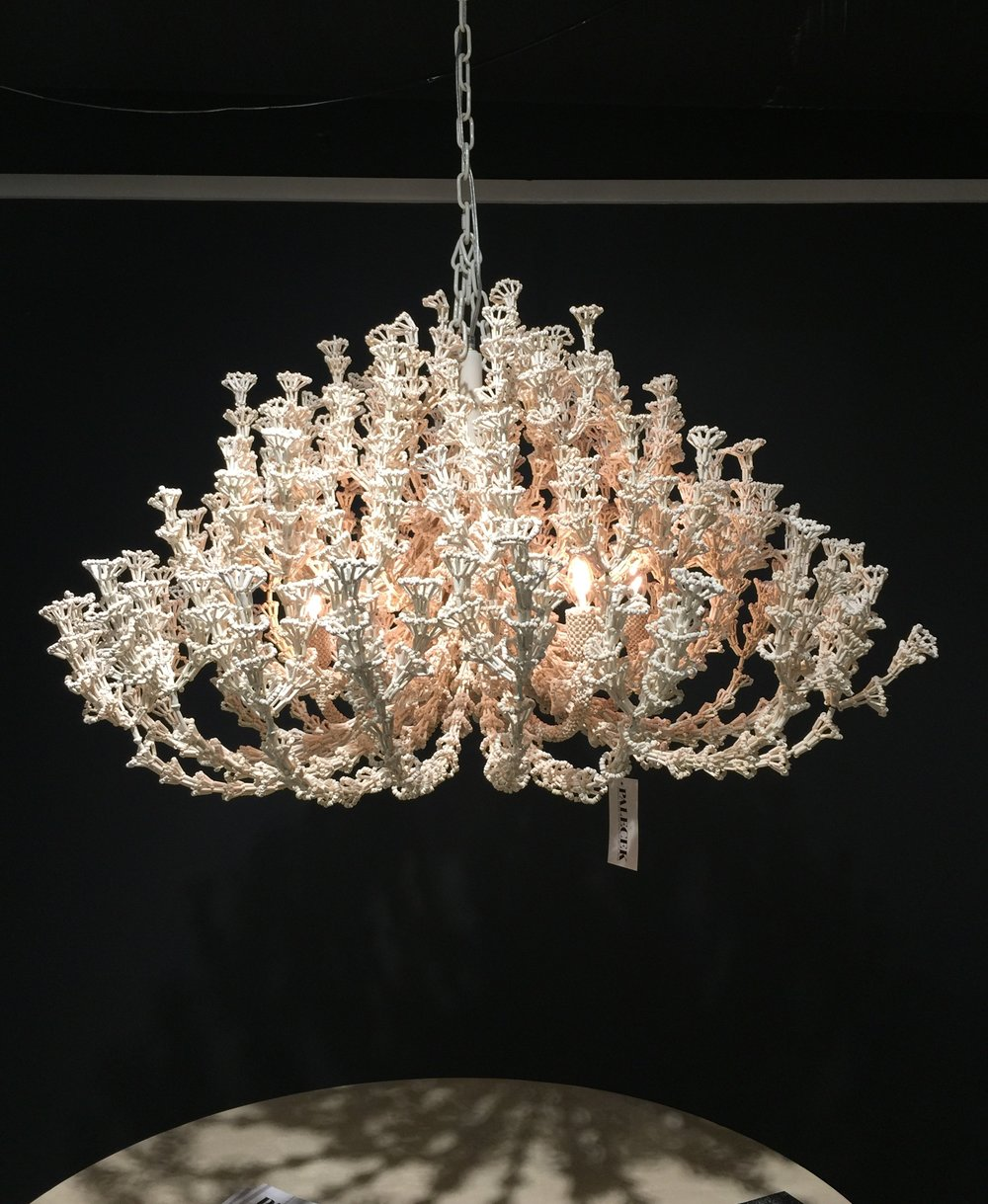 Stunning shell bead chandelier against a black wall in the Palacek showroom