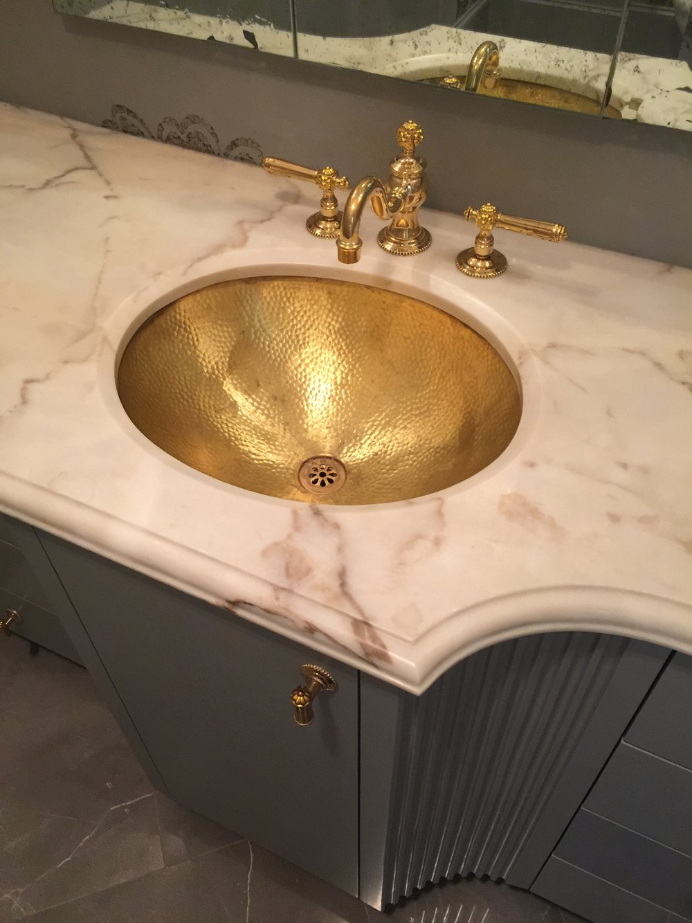 Lovely powder room with brass accents designed by Beth Lindsey