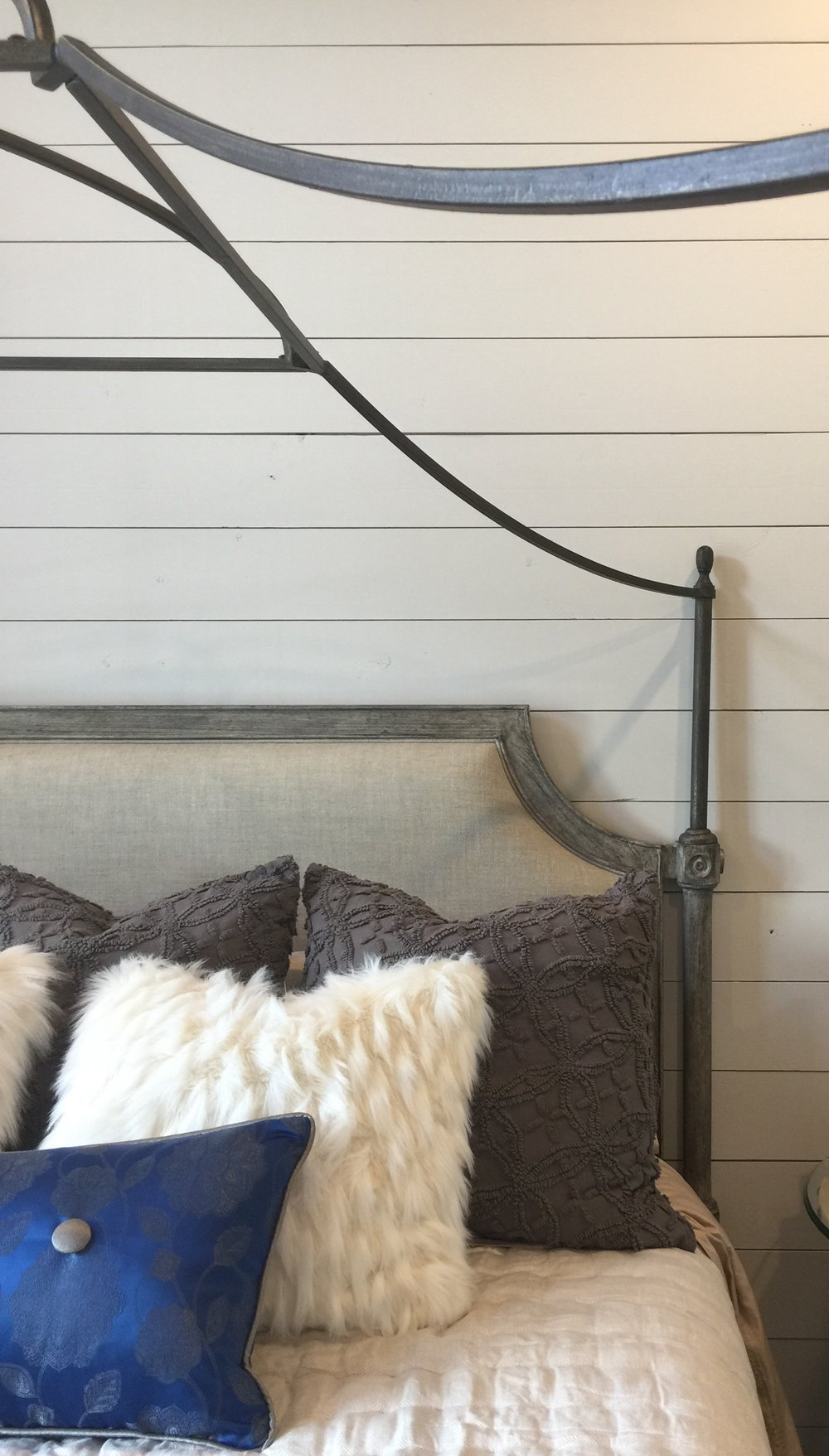 Shiplap wall with curvy iron bed in bedroom designed by Christina Mullen