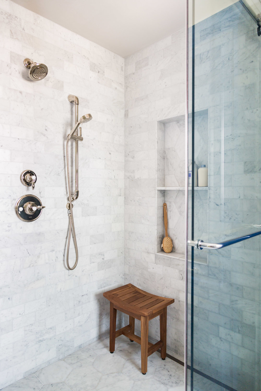 Vintage Carrara marble shampoo niche with linear drain in bathroom remodel Carla Aston Designer