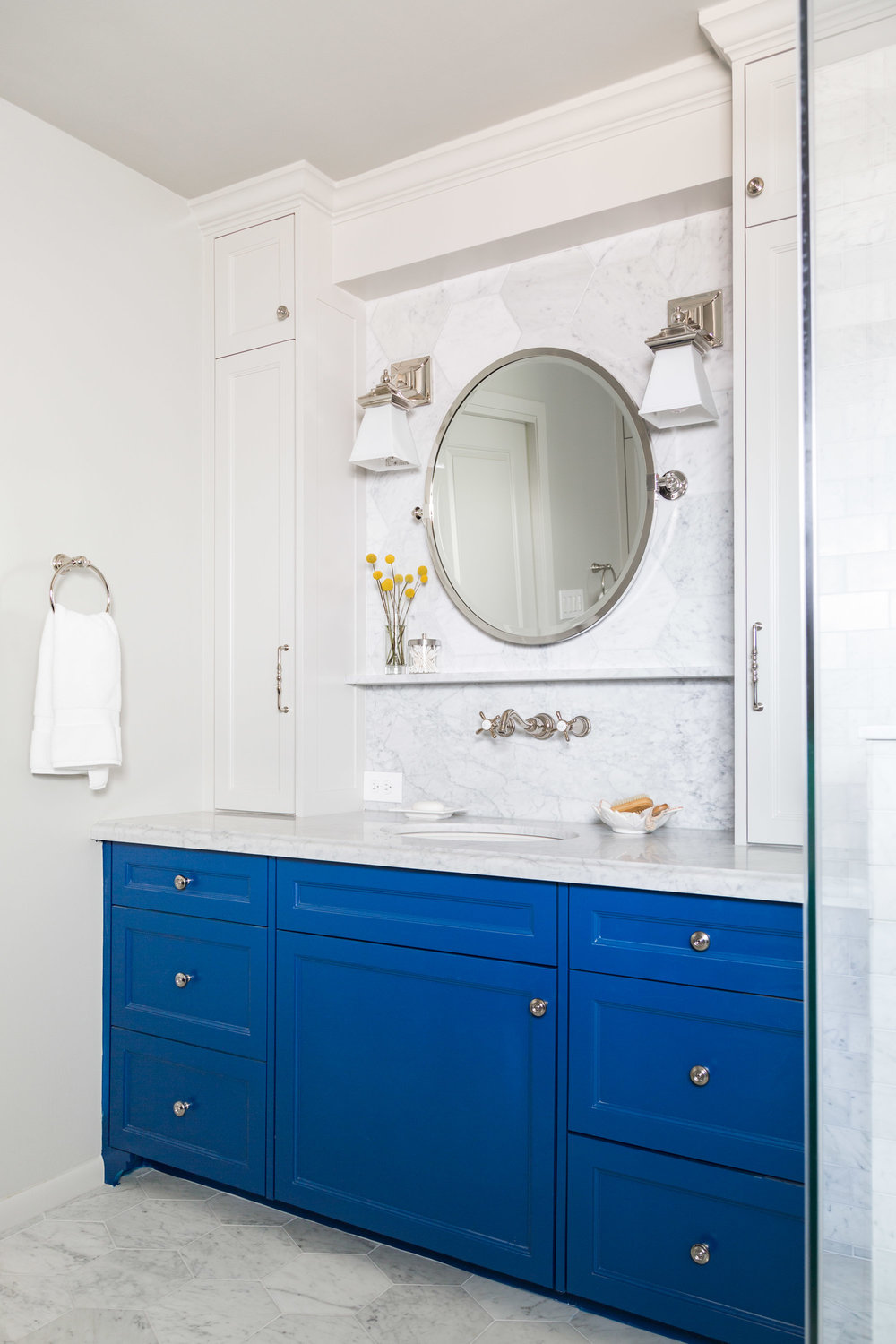 Pivot mirror and wall mount faucet at vanity with hex marble tile | Carla Aston, Designer | Tori Aston, Photographer  #bathroomremodel #marblebathroom #hextile #bluecabinets