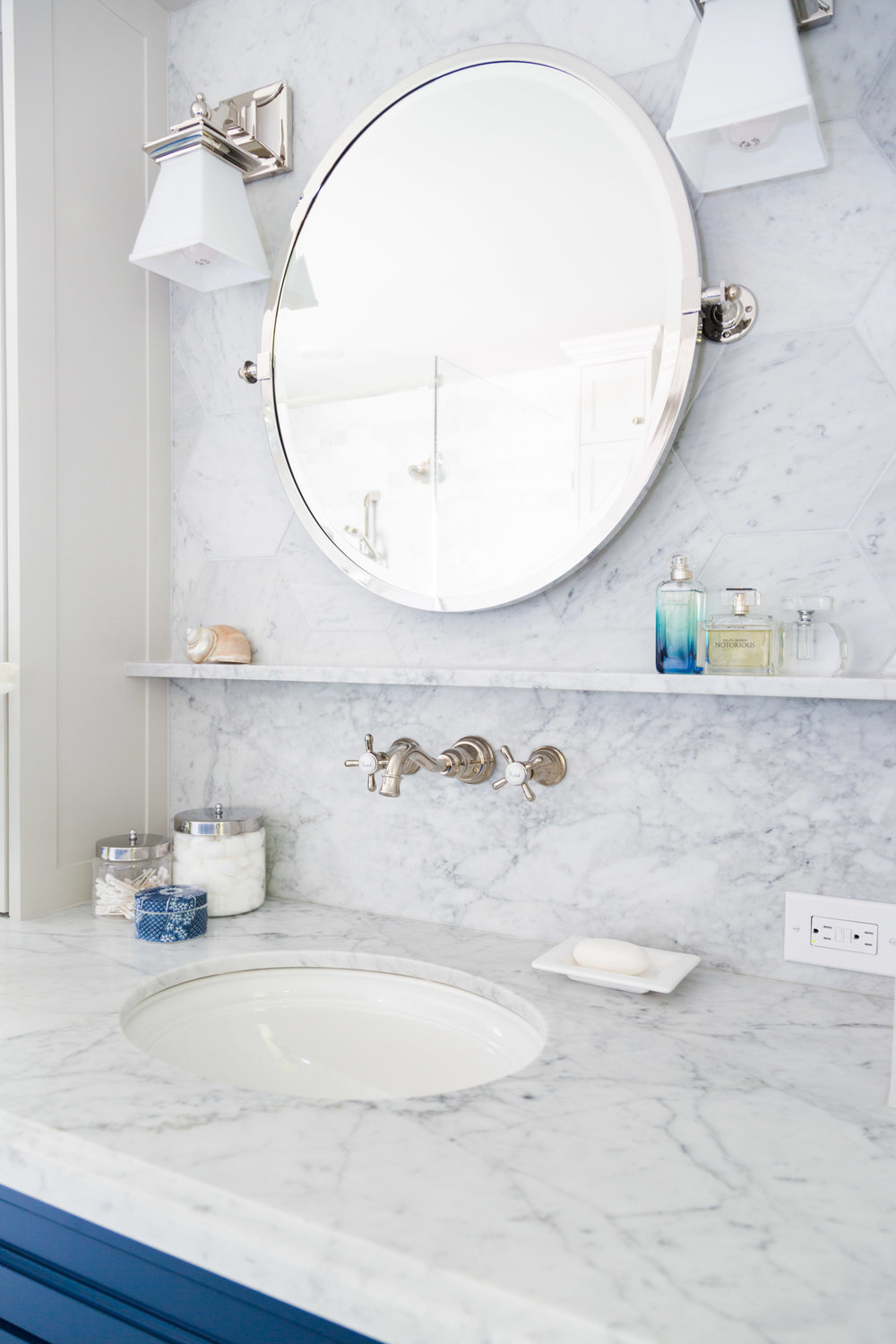 Marble ledge and wall mount faucet with pivot mirror at master bathroom vanity | Carla Aston, Designer | Tori Aston, Photographer #bathroomremodel #marblebathroom #hextile #bluecabinets