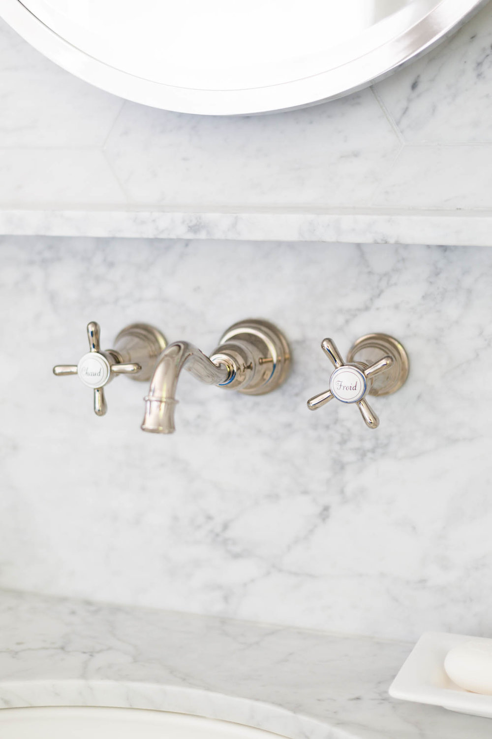 Wall mount faucet on white marble backsplash with ledge at bathroom sink | Carla Aston, Designer | Tori Aston, Photographer
