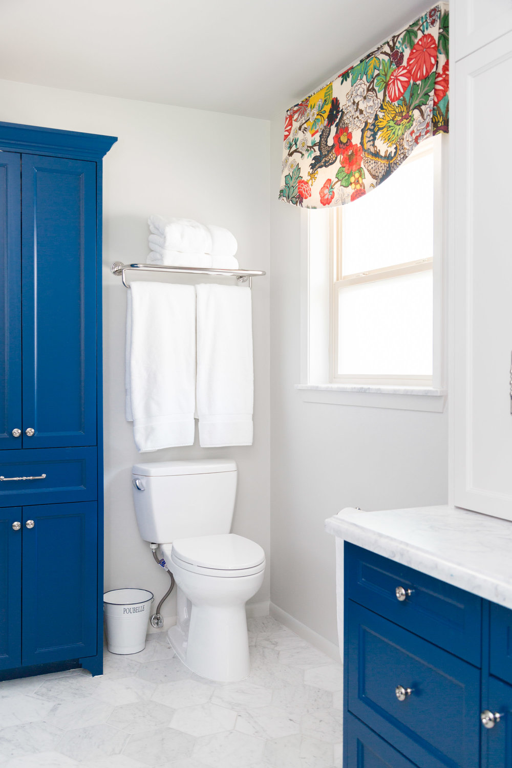 Navy blue cabinetry with Schumacher Chiang Mai Dragon fabric valance window treatment | Carla Aston, Designer | Tori Aston, Photographer  #bathroomremodel #marblebathroom #hextile #bluecabinets