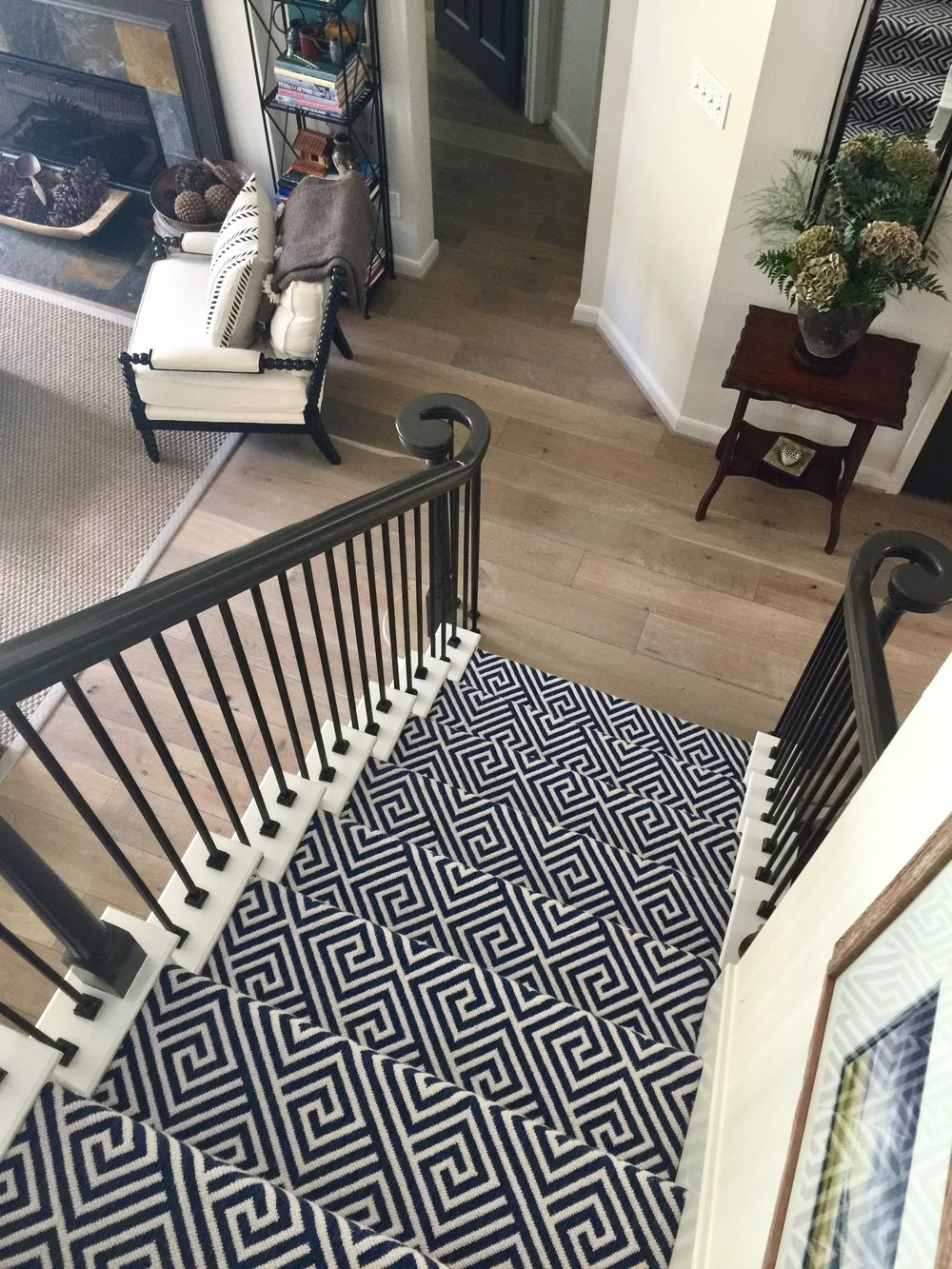 Patterned stair carpet in center of open plan home with wood bottom step - Designer Carla Aston #stairrunner