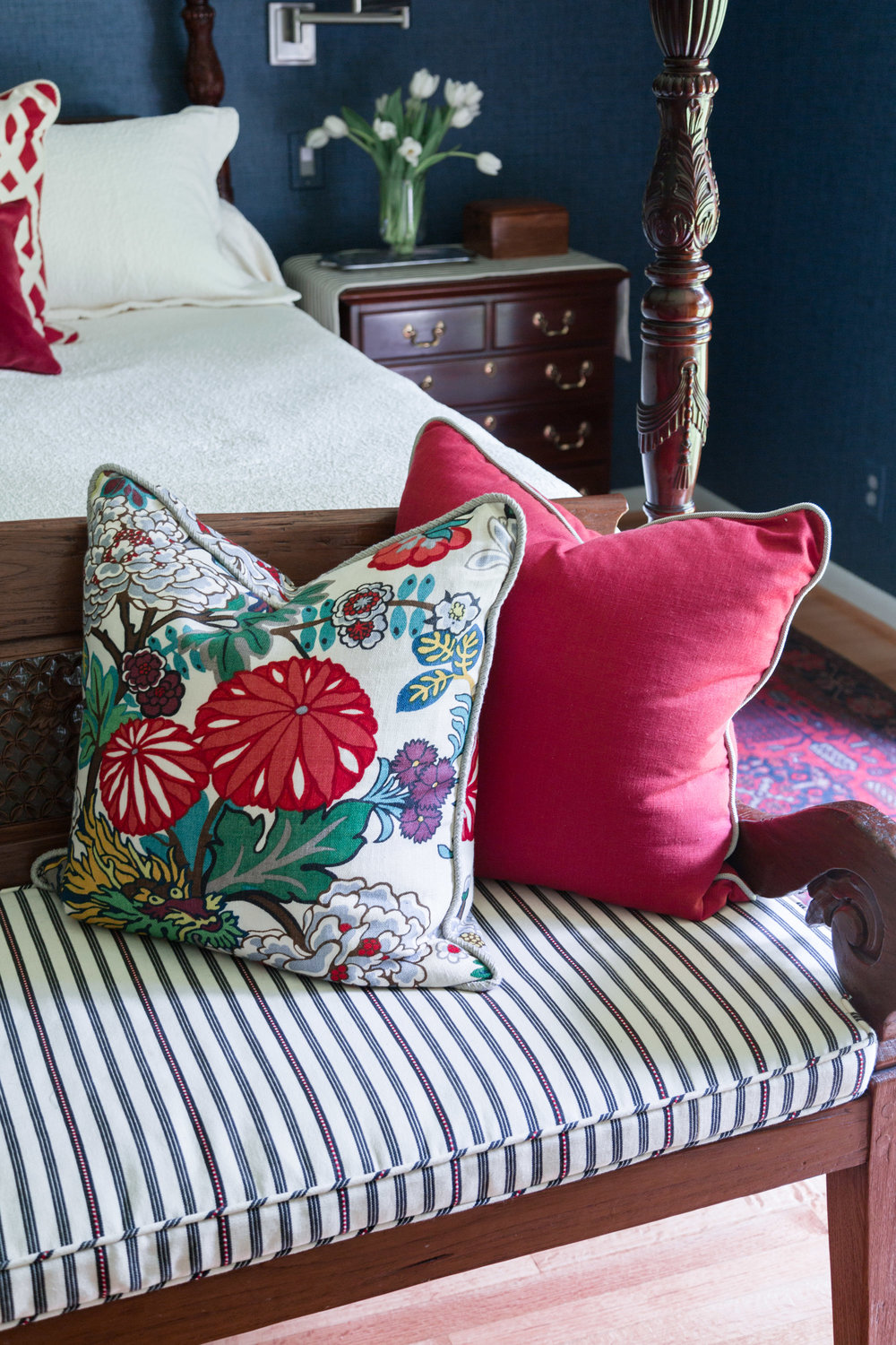 Bench at end of bed with red pillow and Chiang Mai fabric, Designer: Carla Aston