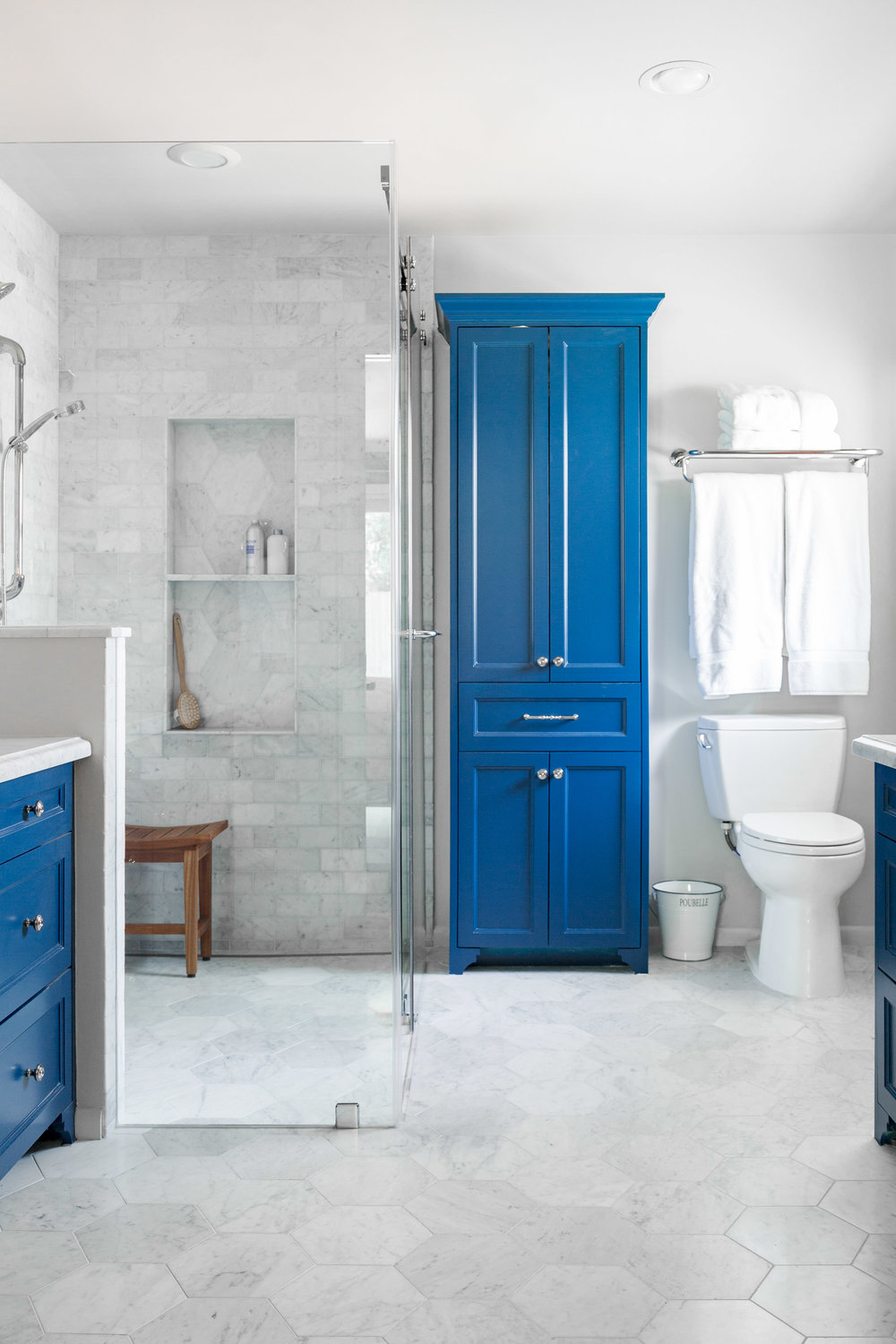 Bathroom remodel with white Carrara marble and blue cabinets Designer: Carla Aston