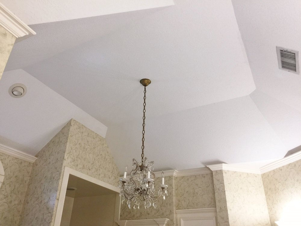 BEFORE - Many angles and planes are accentuated at the ceiling with crown moulding and wallpaper.
