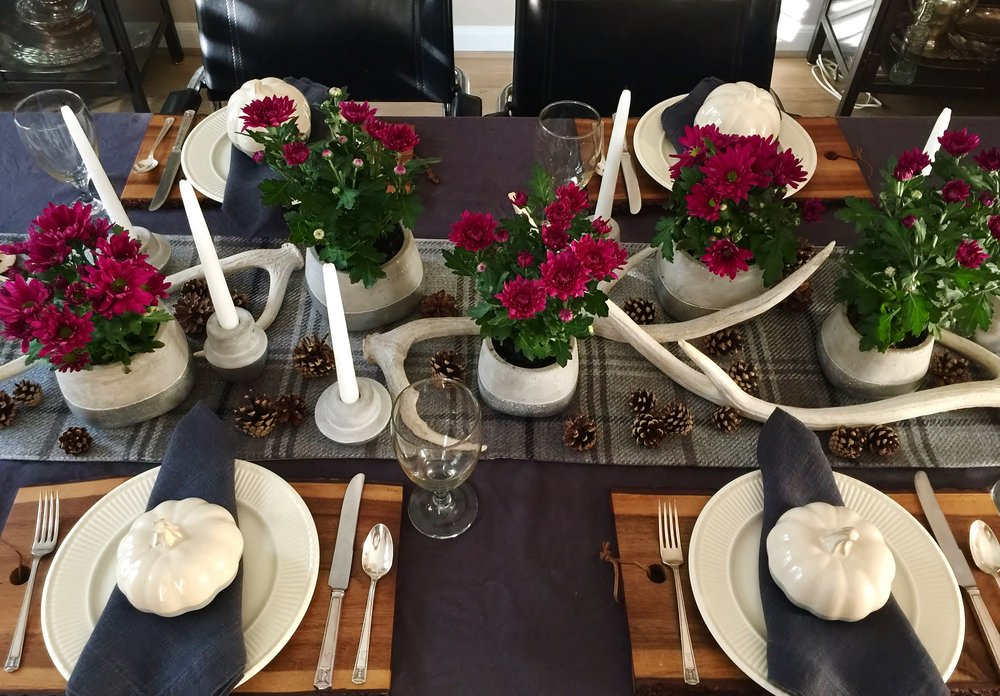 Dining room table setting with centerpiece for Thanksgiving
