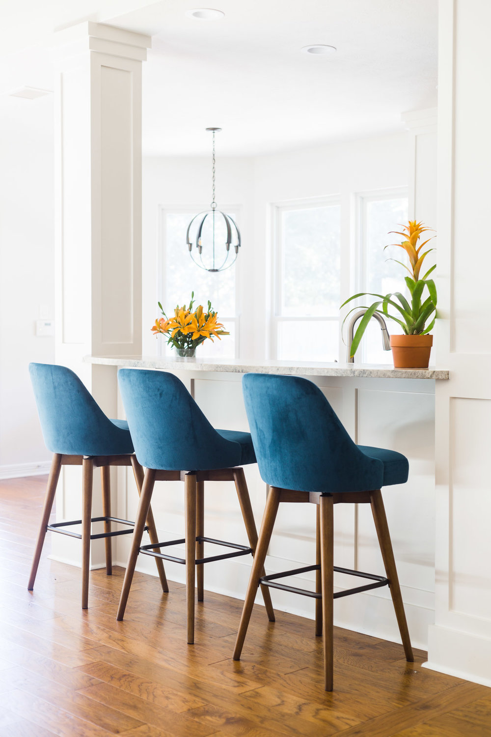 Mid century modern bar stools with white paneling at kitchen bar, kitchen remodel, Designer: Carla Aston