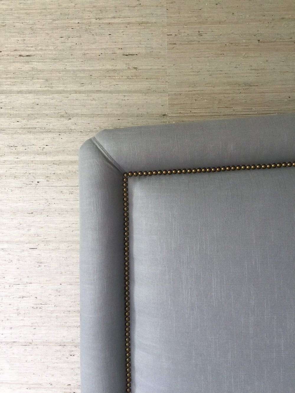 Upholstered headboard on grasscloth wall