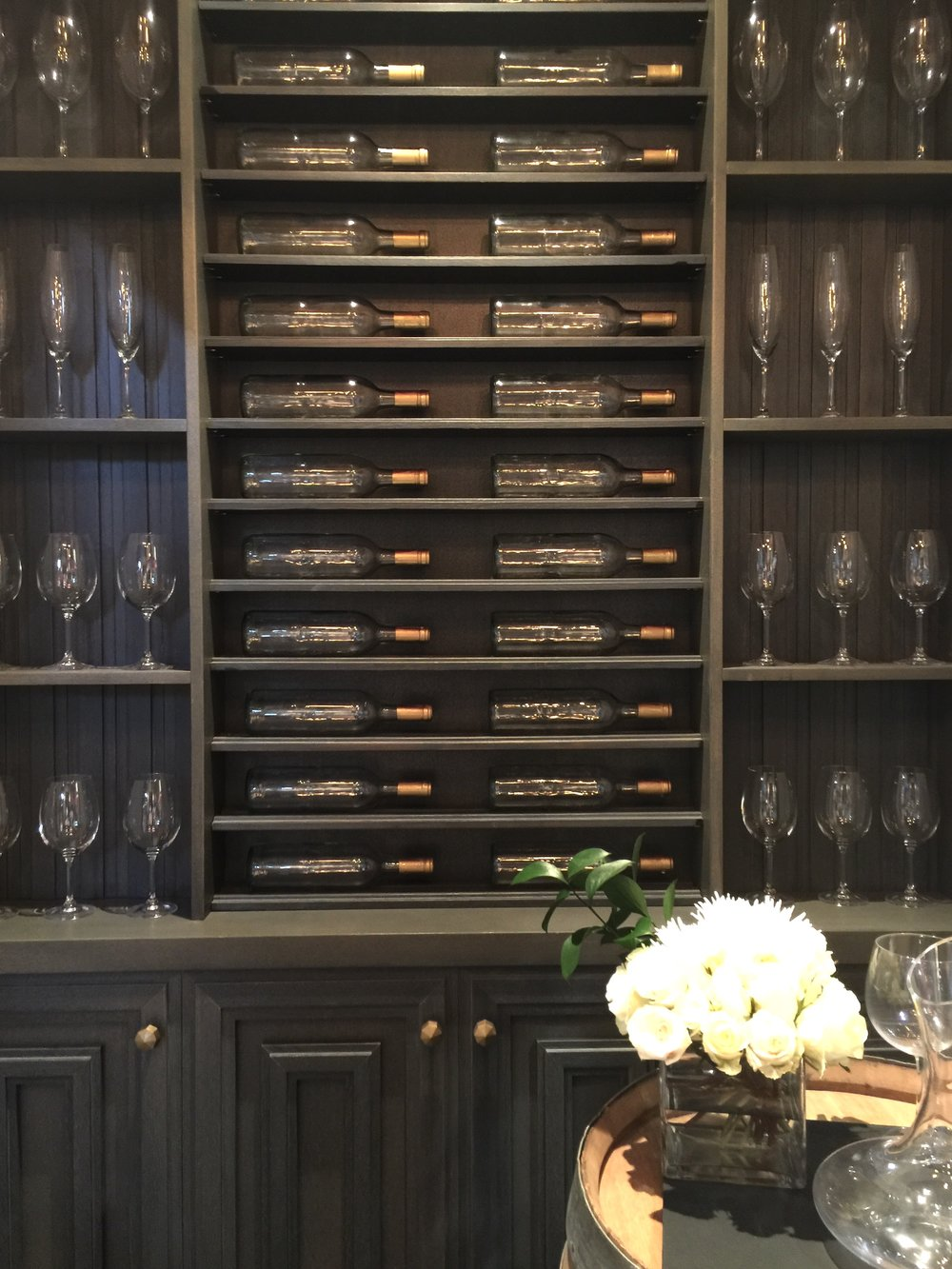 These mouldings and panelings were ingeniously put together on this wall to create some beautiful wine storage with a paneled look. #wineroom #mouldings