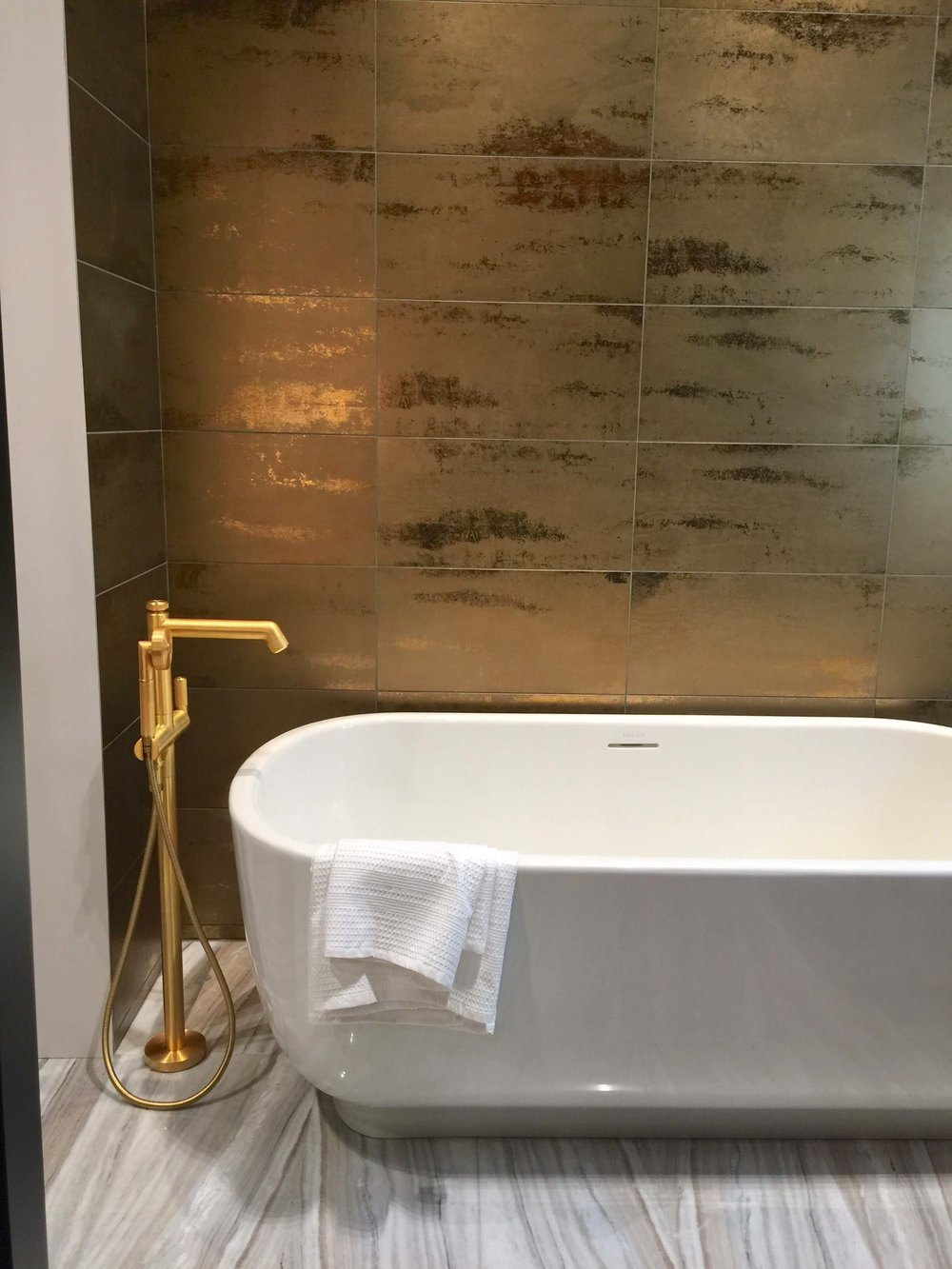 There was lots of gold and brushed brass at the show. Here at Ann Sacks, this tiled wall was a real stunner! #gold #goldtile #tile #bathroom