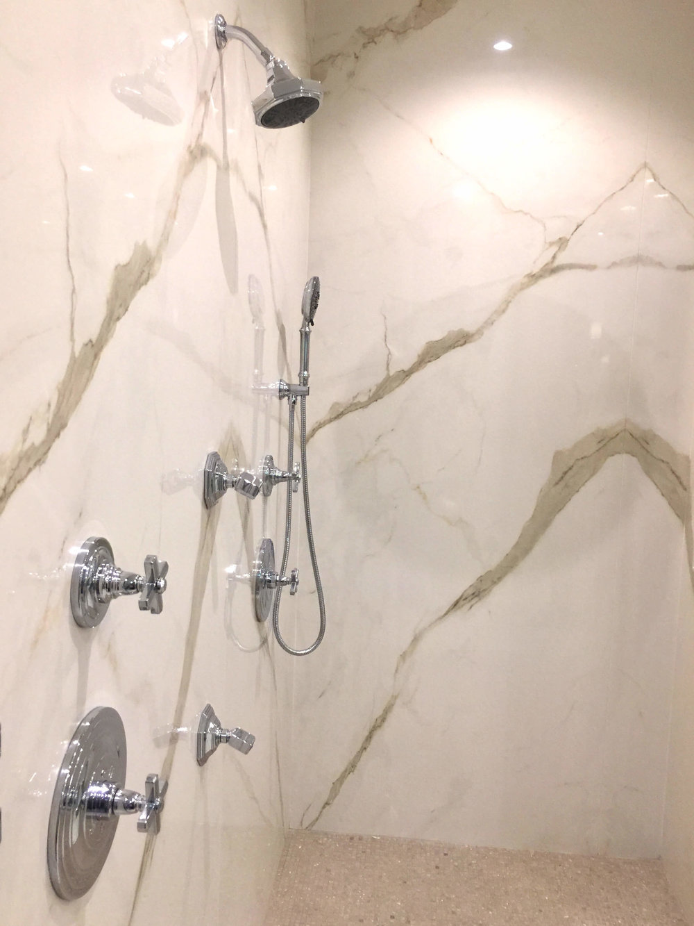The master shower was lined with porcelain slabs, a great alternative to tile. No grout! The New American Remodel - Orlando, KBIS2018 #masterbathroom #bath #bathroomdesign #showerstall