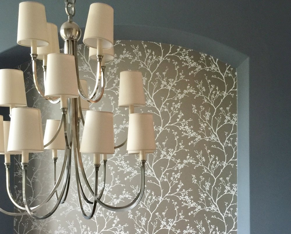 Dining room with wallpaper and silver chandelier