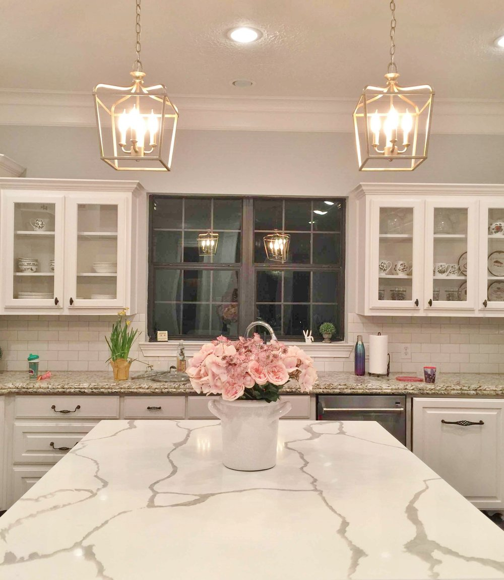 AFTER - The new white marble kitchen island countertop brightens the center of this kitchen #marblecountertop #whitekitchen