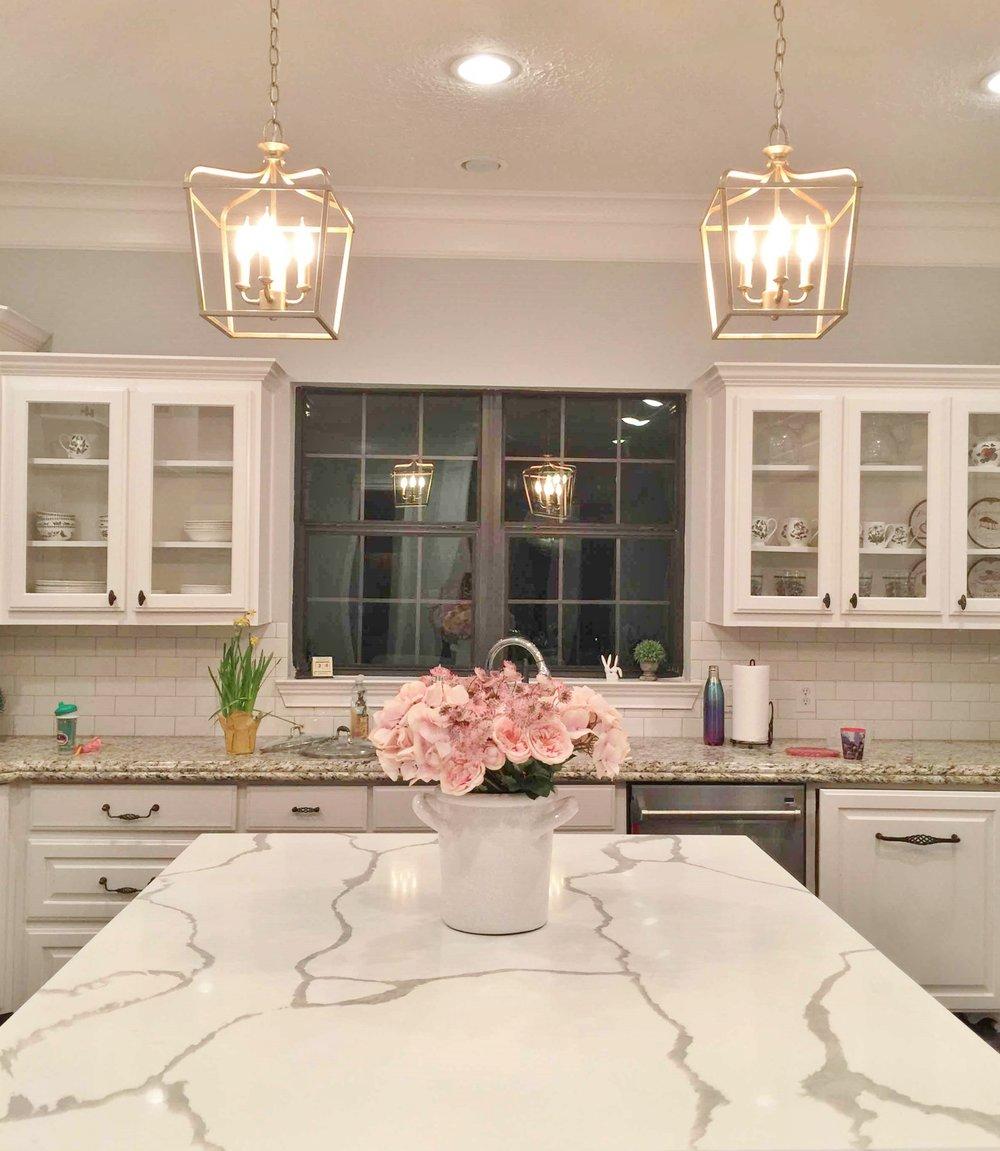 AFTER - The new white marble kitchen island countertop brightens the center of this kitchen #marblecountertop #whitekitchen